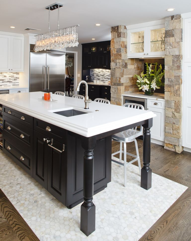 Natural stone columns frame inset wine bar cabinets and refrigerator ...