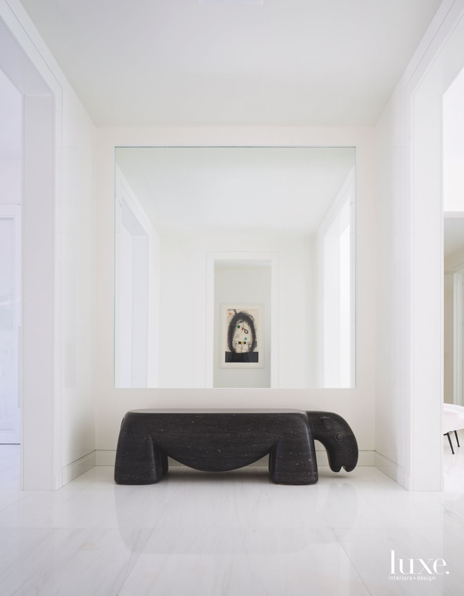 Abstract Bench and Artwork Mirror Reflection in White Hallway