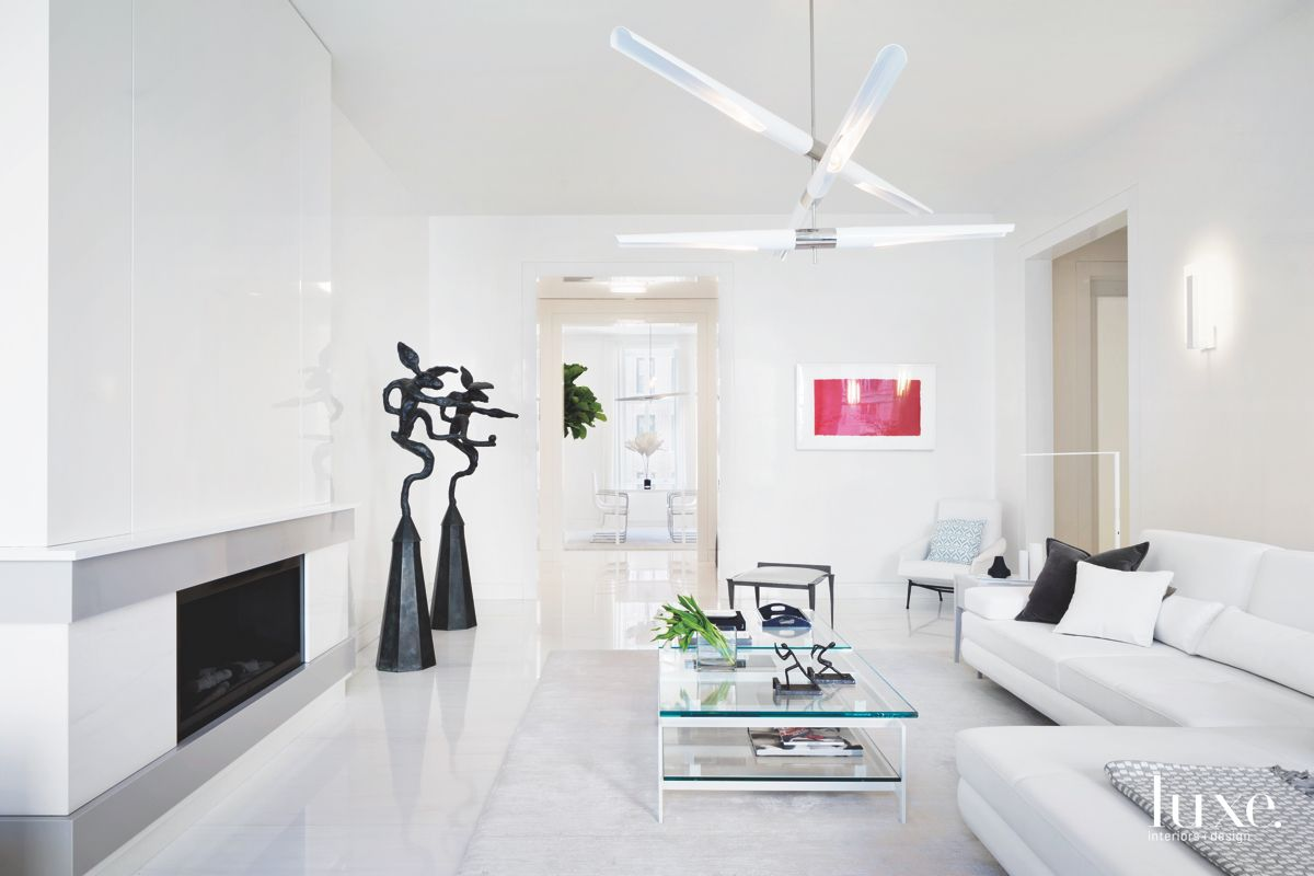 All White Sleek Living Room with Fireplace Artwork and Whimsical Lighting