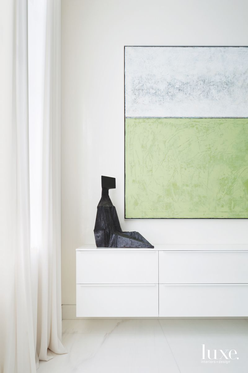 Green and White Artwork with Sitting Sculpture Hallway