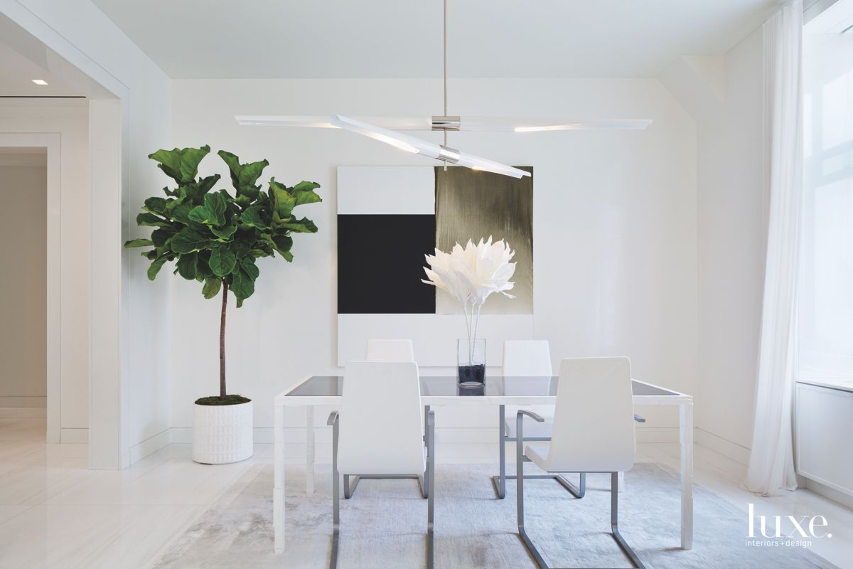White Dining Room with Large Tree Plant and Abstract Artwork