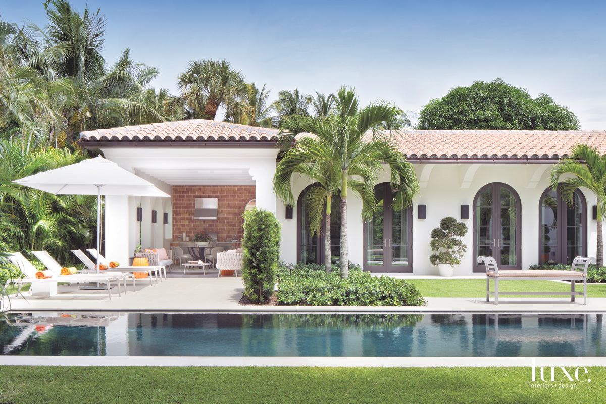 Classic Florida Exterior with Lap Pool, Palm Trees, and Lounge Area