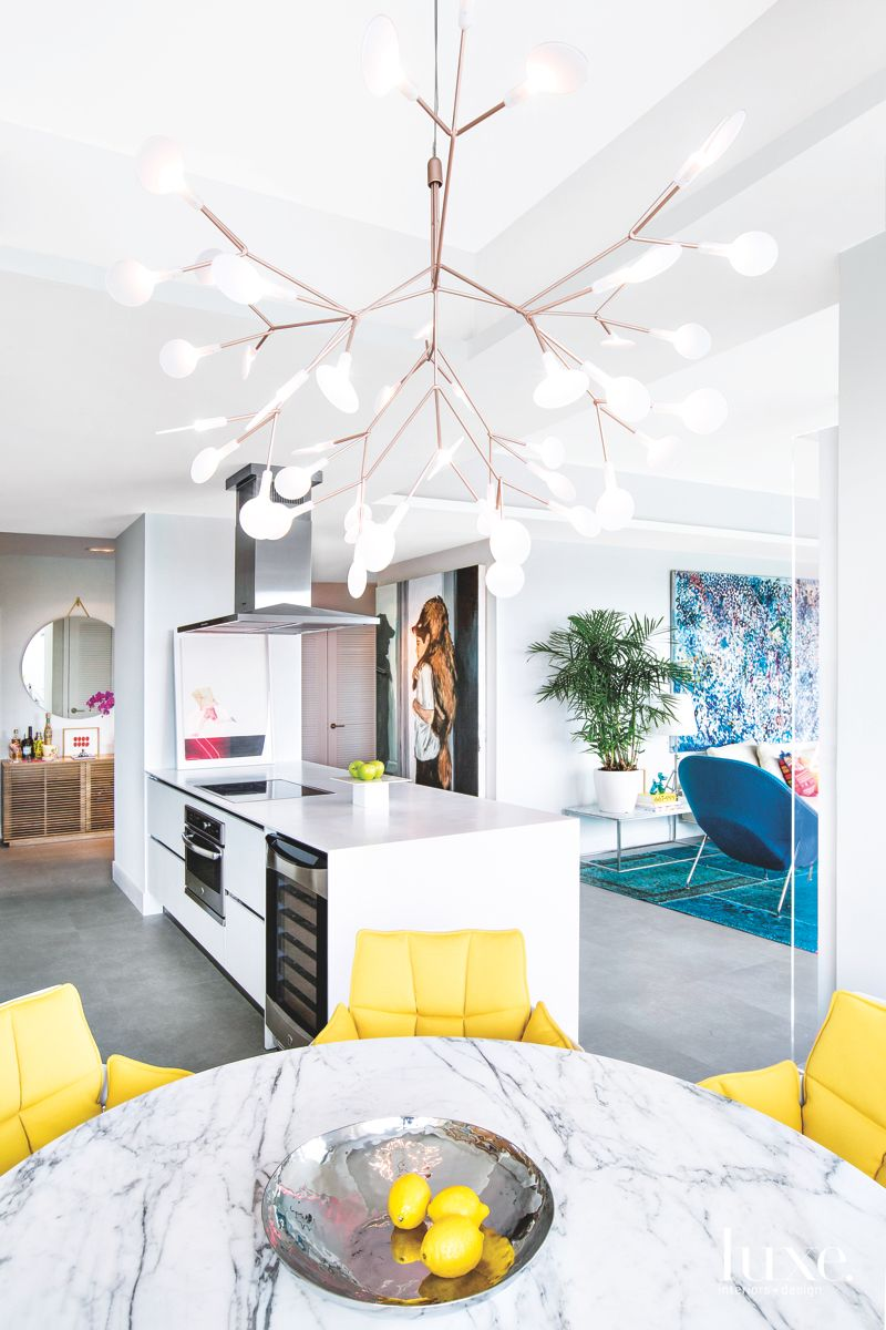 Open Kitchen with Chandelier, Yellow Chairs and Wine Rack