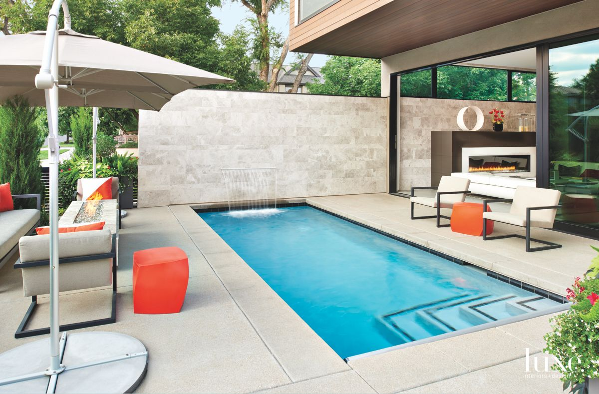 Water Feature Pool with Orange Ottomans, Umbrella, and Fireplace