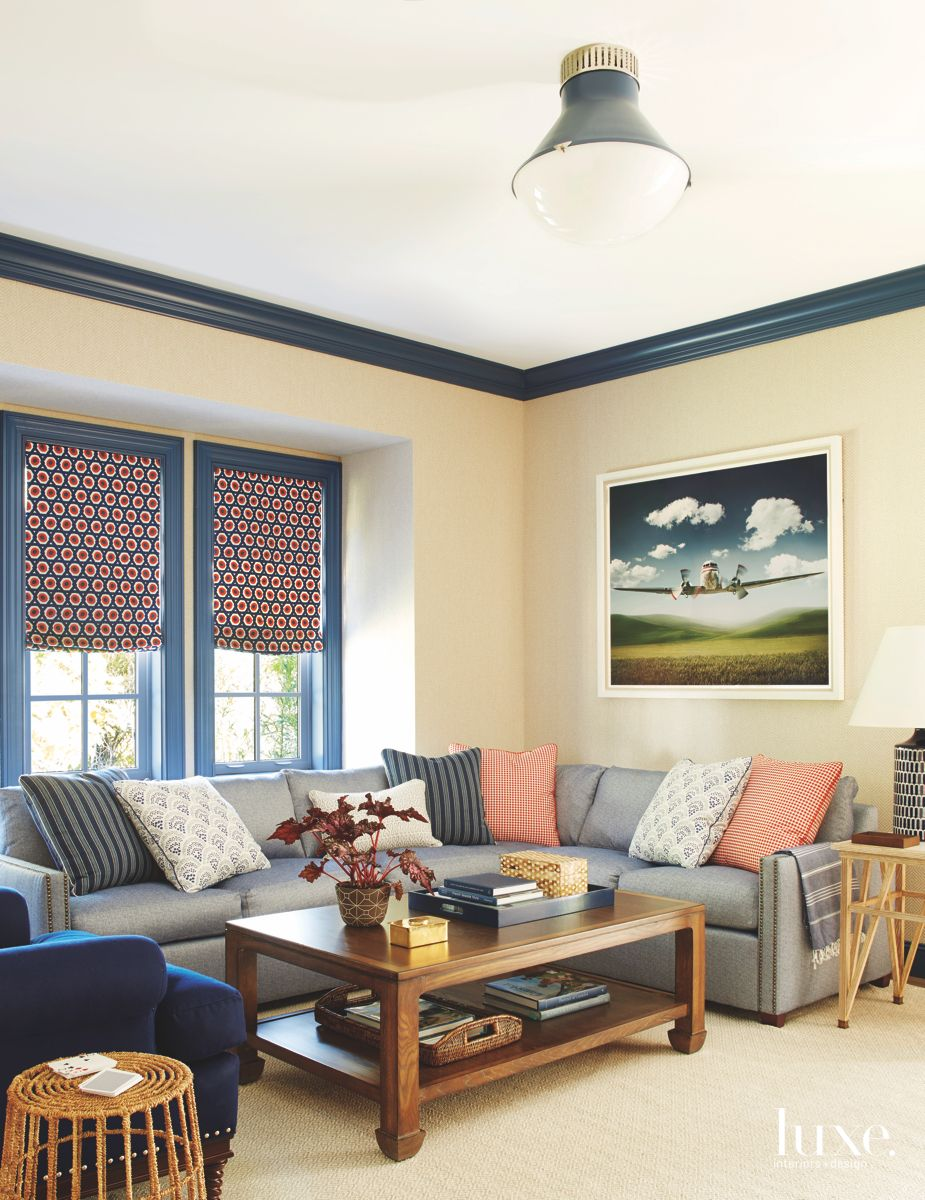 Cream and Blue Family Room with Airplane Art and Patterned Curtains