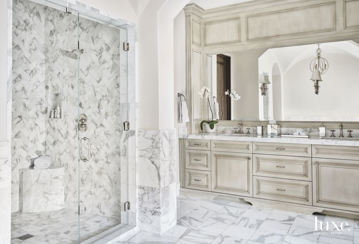 Patterned Marble with Chandelier and Custom Cabinets in the Master Bathroom