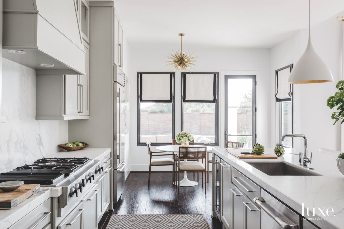 Chrome and White Kitchen with Chandelier Dining Area View