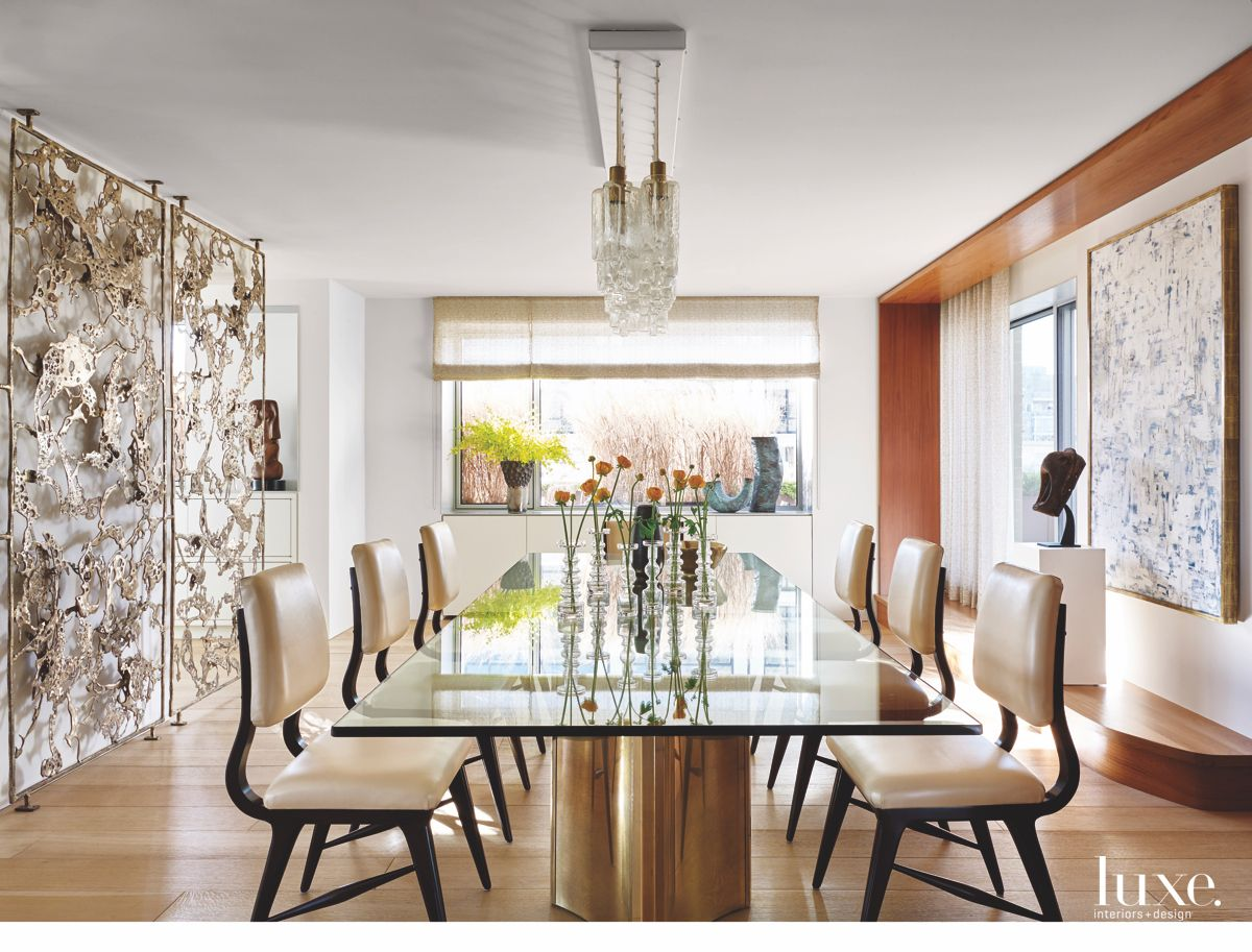 Layered Abstract Bronze Screen Dining Room with Artwork and Chandelier