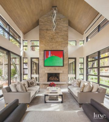Lovely High Vaulted Ceiling Living Room With Stone Fireplace And Dangling Artwork