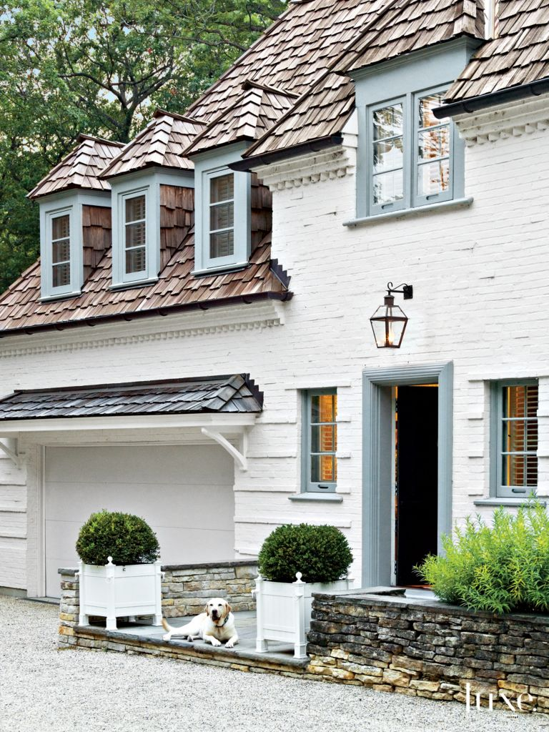 Traditional White Brick Exterior with Boxwoods - Luxe Interiors + Design