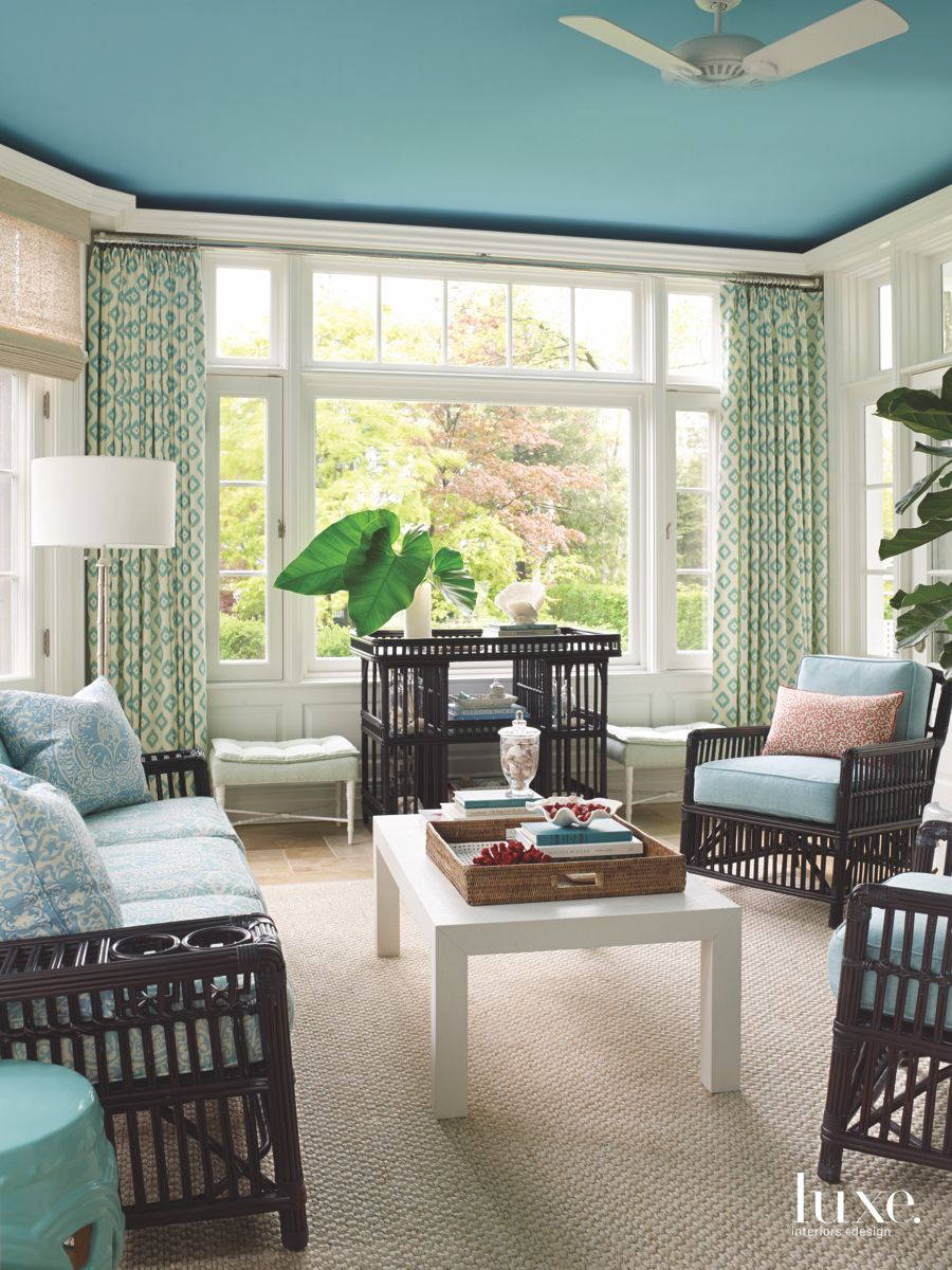 Blue Island Vibe Sunroom with Patterned Curtains and Wicker Furniture