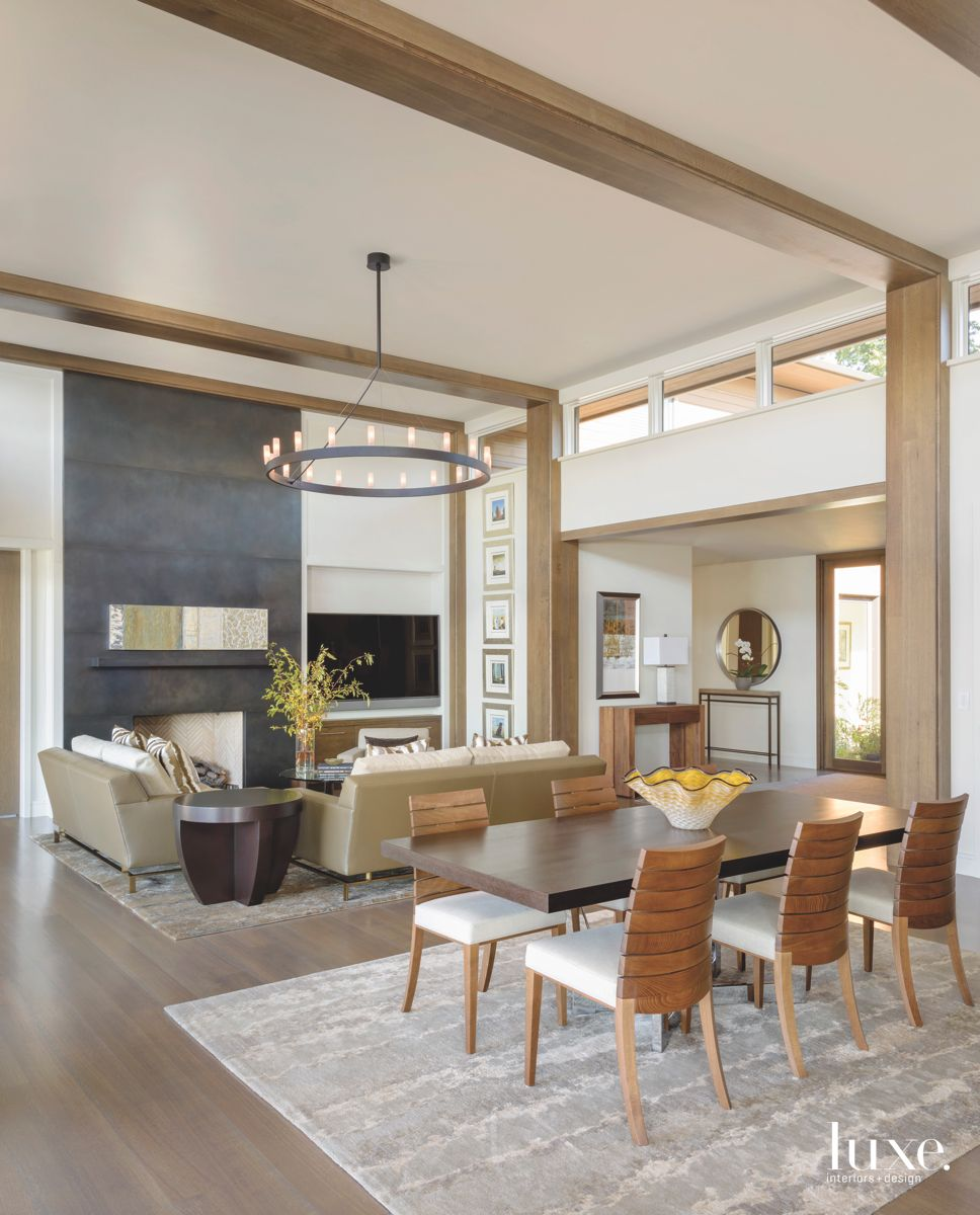 Slate Fireplace Central Living Room with Contemporary Chandelier and Wooden Chairs