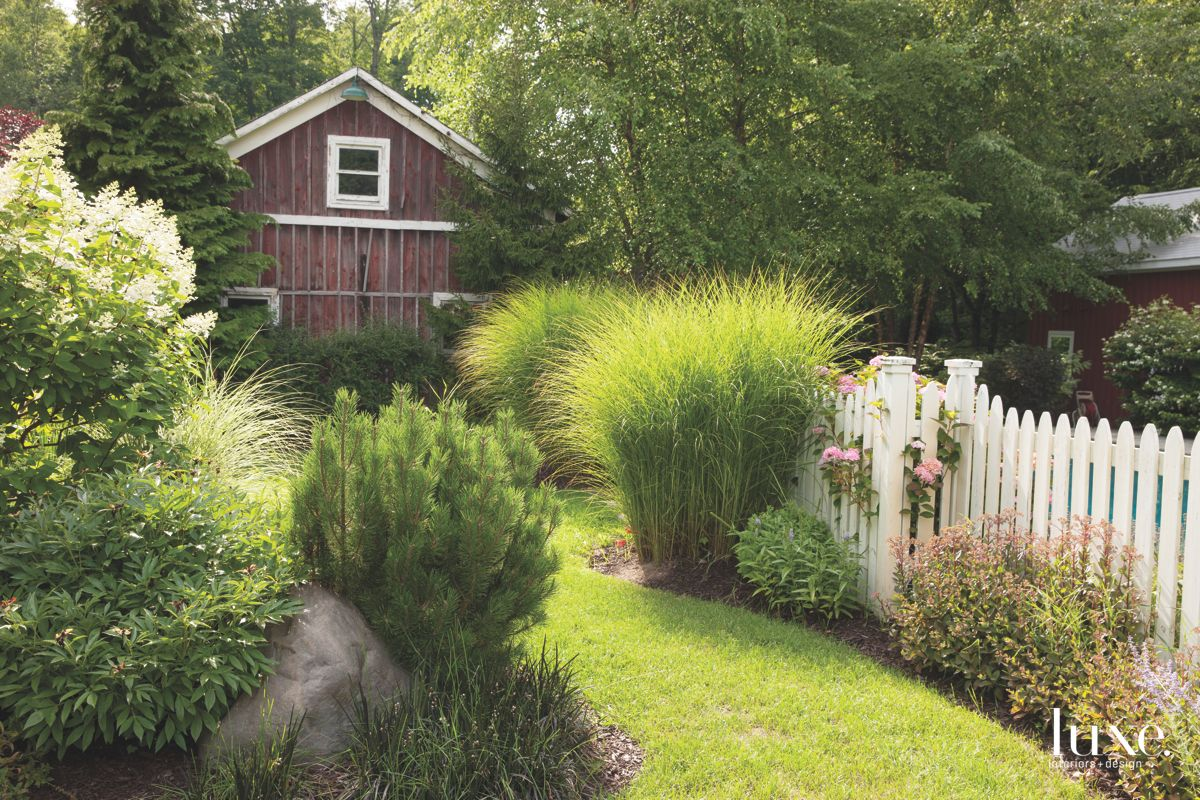 Barn Guesthouse with Garden Shrubs and White Picket Fence