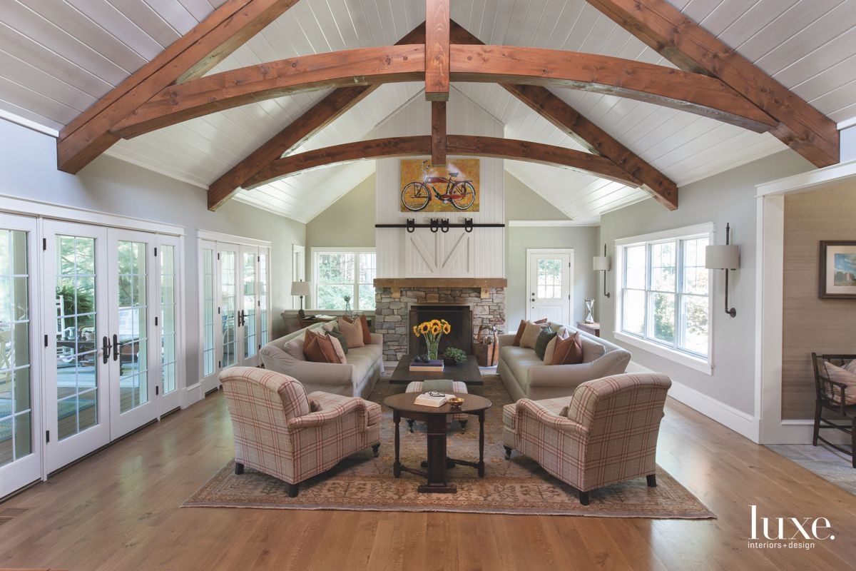 Wooden Beam Arched Ceiling with Barn Doors, Fireplace, and Bicycle Artwork
