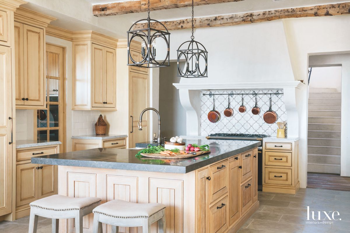 Old-World Inspired Kitchen with Chandeliers and Hand-Painted Tile Backsplash