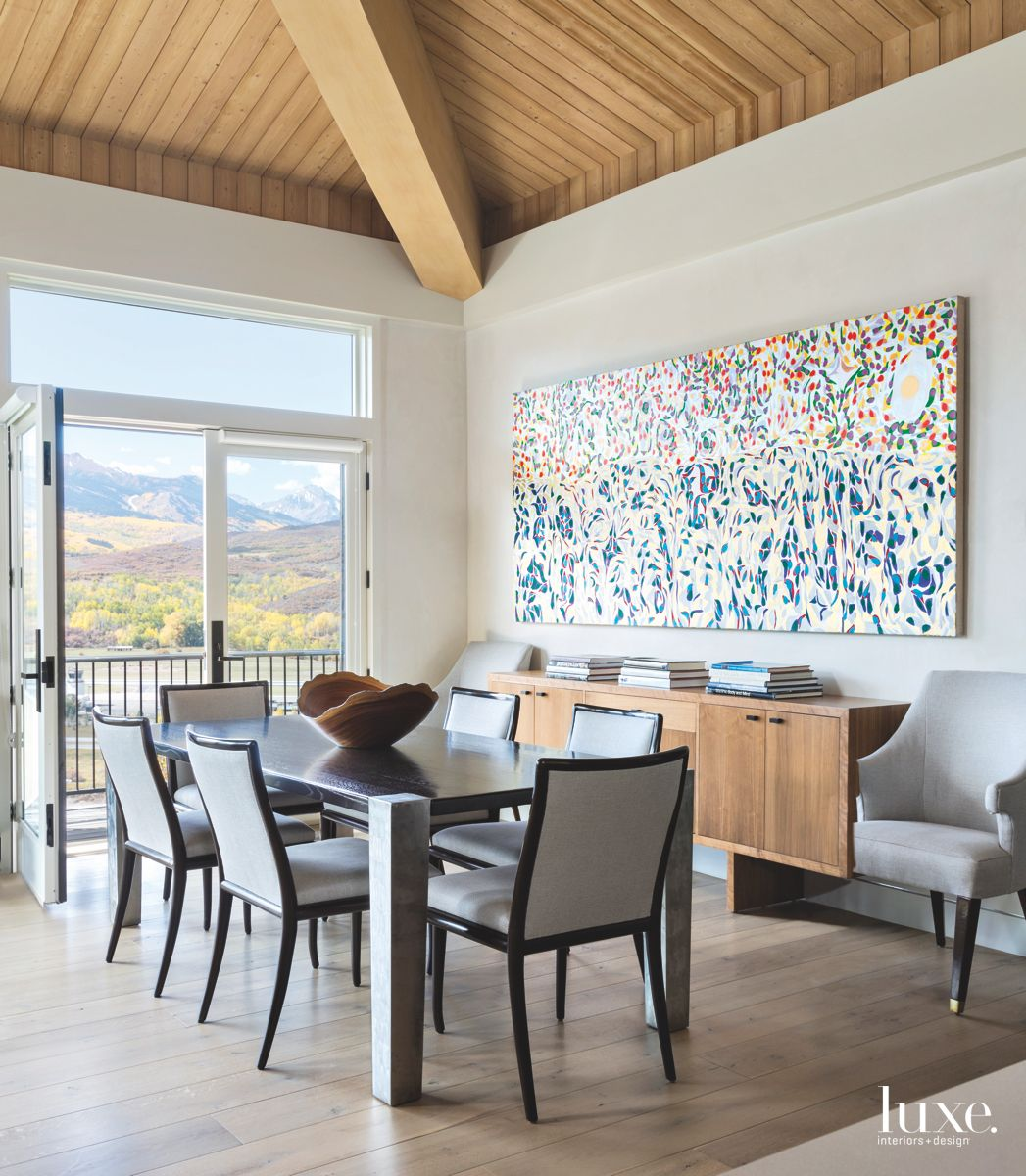 Multi-Colored Artwork Dining Room with Modern Chairs and Vaulted Ceiling