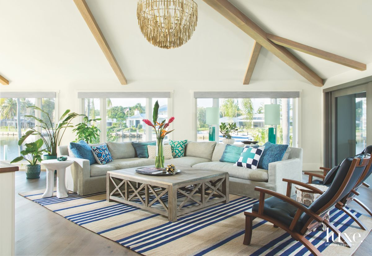 Nautical Rope Chandelier Living Room with Blue Striped Rug and Wooden Table with High Ceilings