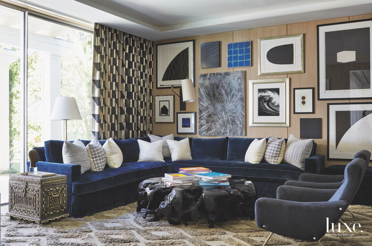 Lots of Black and White Artwork Wall with Diamond Carpet Pattern and Blue Velvet Sofa
