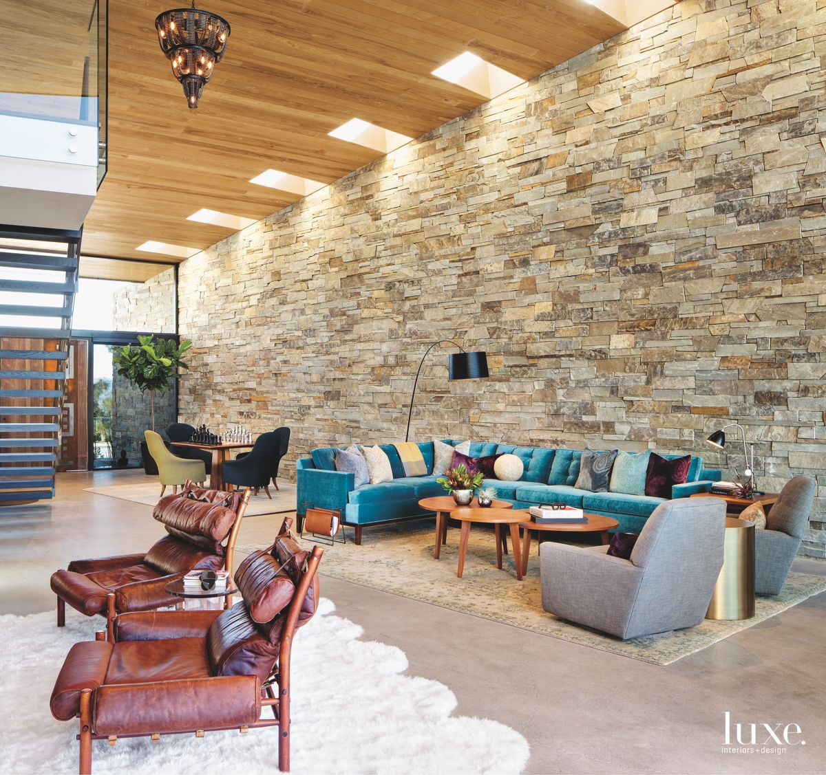 Stone Wall with Toothed Ceiling Great Room with Staircase and Blue Sofa