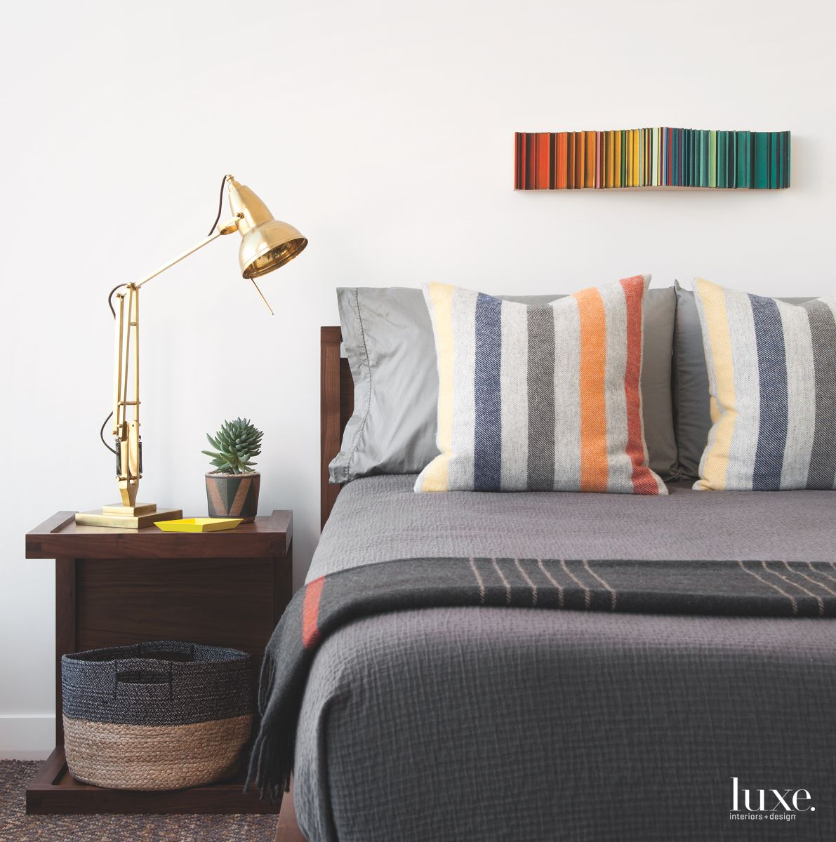 Colorful Wood Artwork Above a Master Bedroom Plush Bed with Lamp