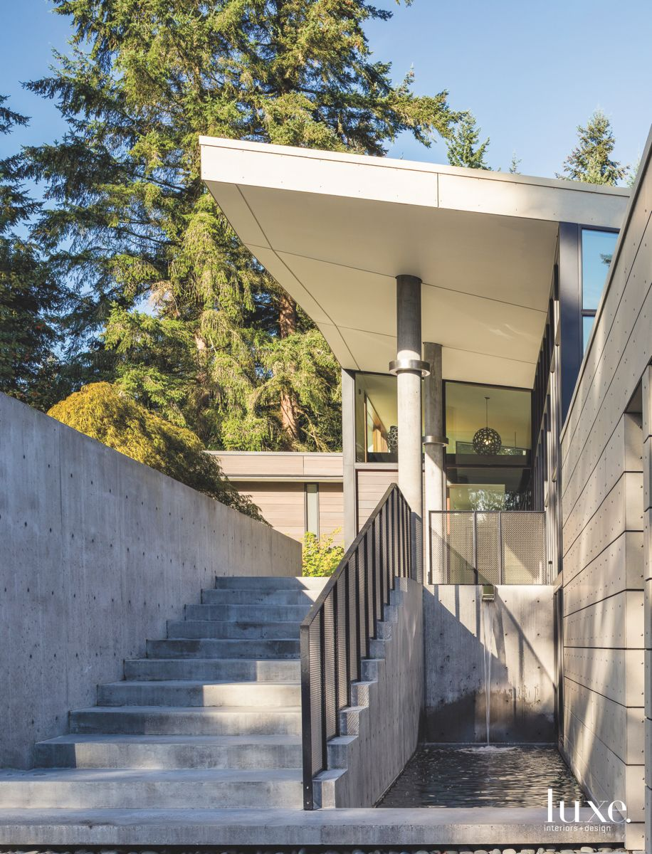 Concrete Stairs Entrance with Water Feature and Steel Railing and Large Tree Background