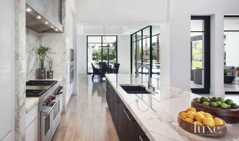 Modern White Kitchen With Limestone Flooring - Luxe Interiors + Design