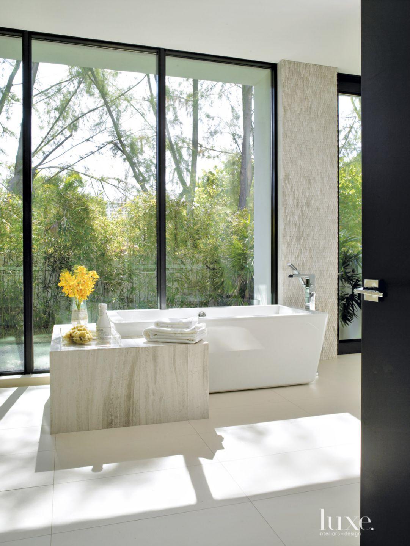 Modern White Bathroom with Vein-Cut Limestone Tub Surround