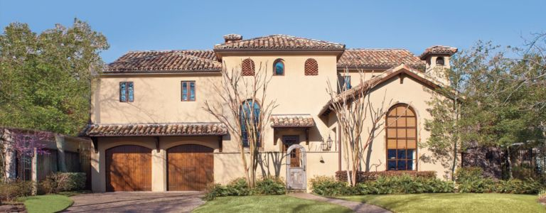 a spanish mediterranean houston mansion with an earthy palette