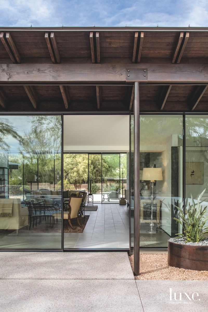 Concrete Entrance to Modernist Living Room with Glass Walls and Plant