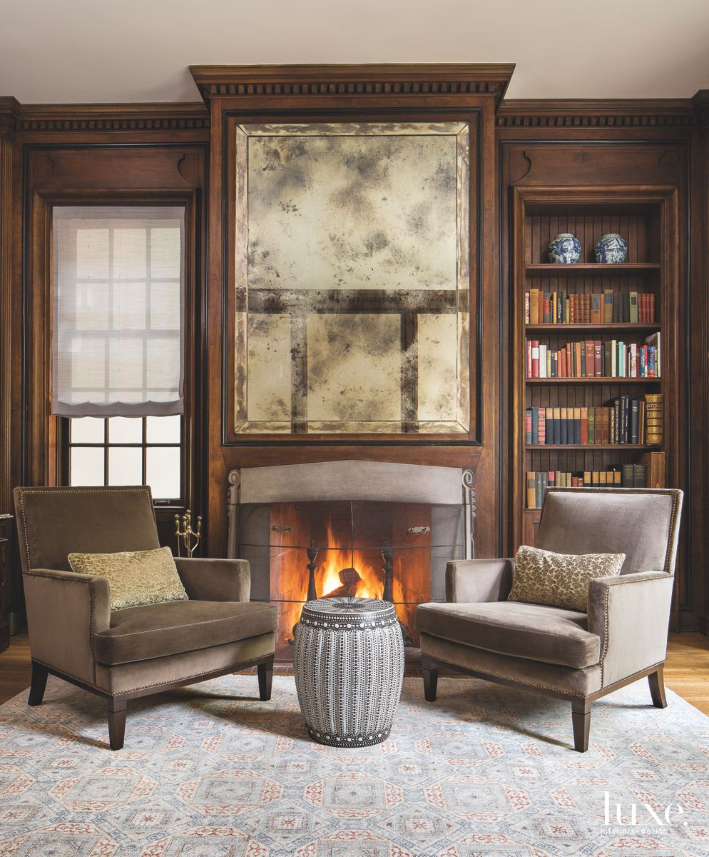 Roaring Fireplace Library with Artwork Twin Chairs and Ottoman Table
