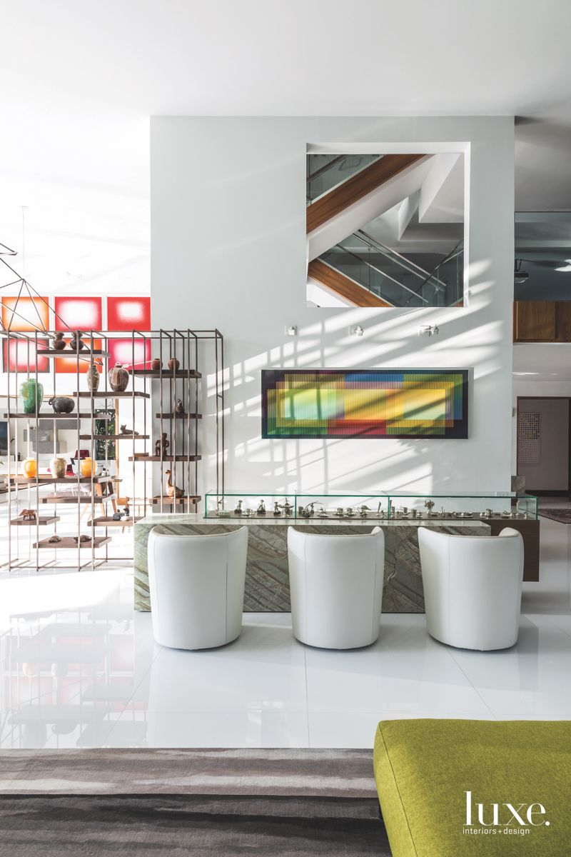 Colorful Artwork and Open Space Wall with White Chairs and Art