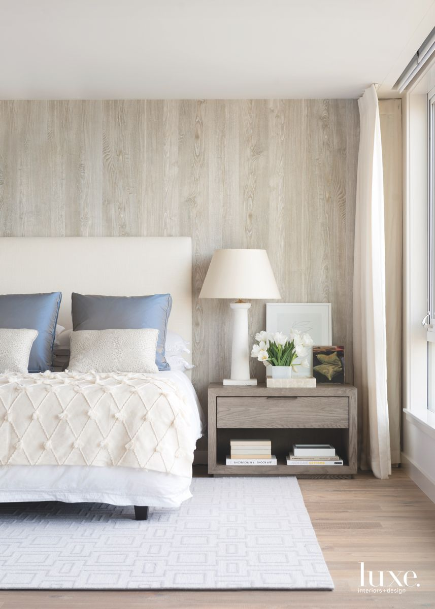 Wood Wall Master Bedroom with Blue Pillows and Textured Bedspread