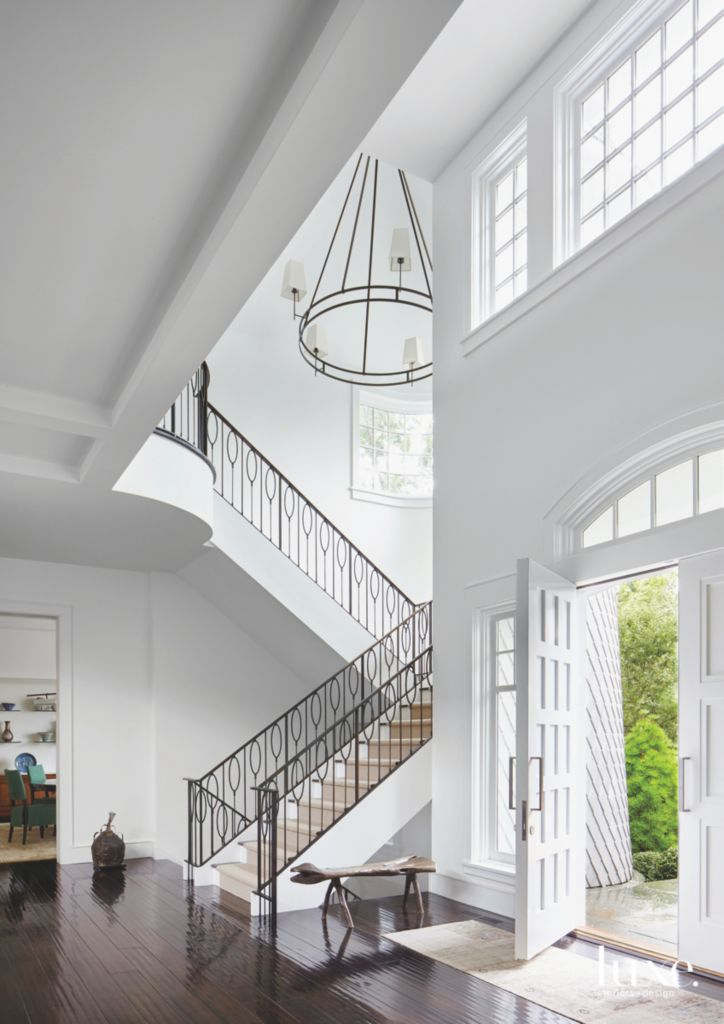 Contemporary Crisp White Entryway With Black Staircase Railing High Ceilings And Chandelier
