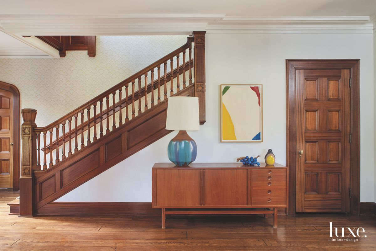Traditional Wooden Staircase Entry Foyer with Table and Modern Art