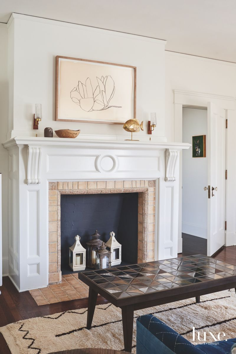 Fireplace Vignette with Lanterns Inside and Hanging Artwork Above