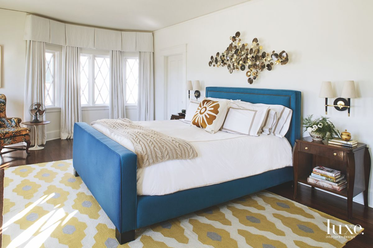 Blue Bed Upholstered Master Bedroom with Patterned Rug and Art Sculpture