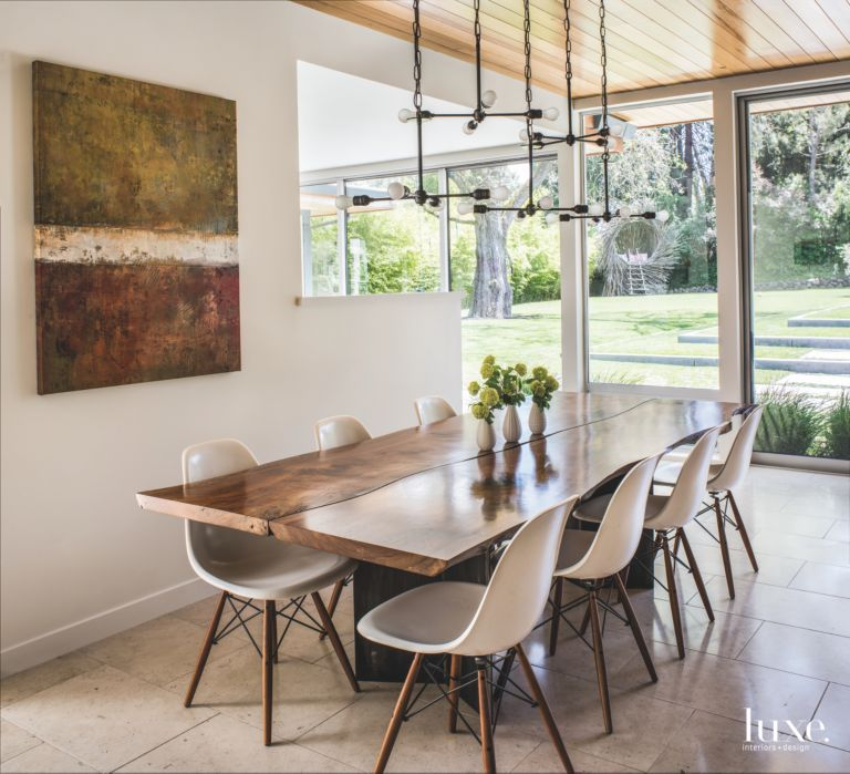 Industrial Lighting Dining Room With Abstract Art And Backyard View