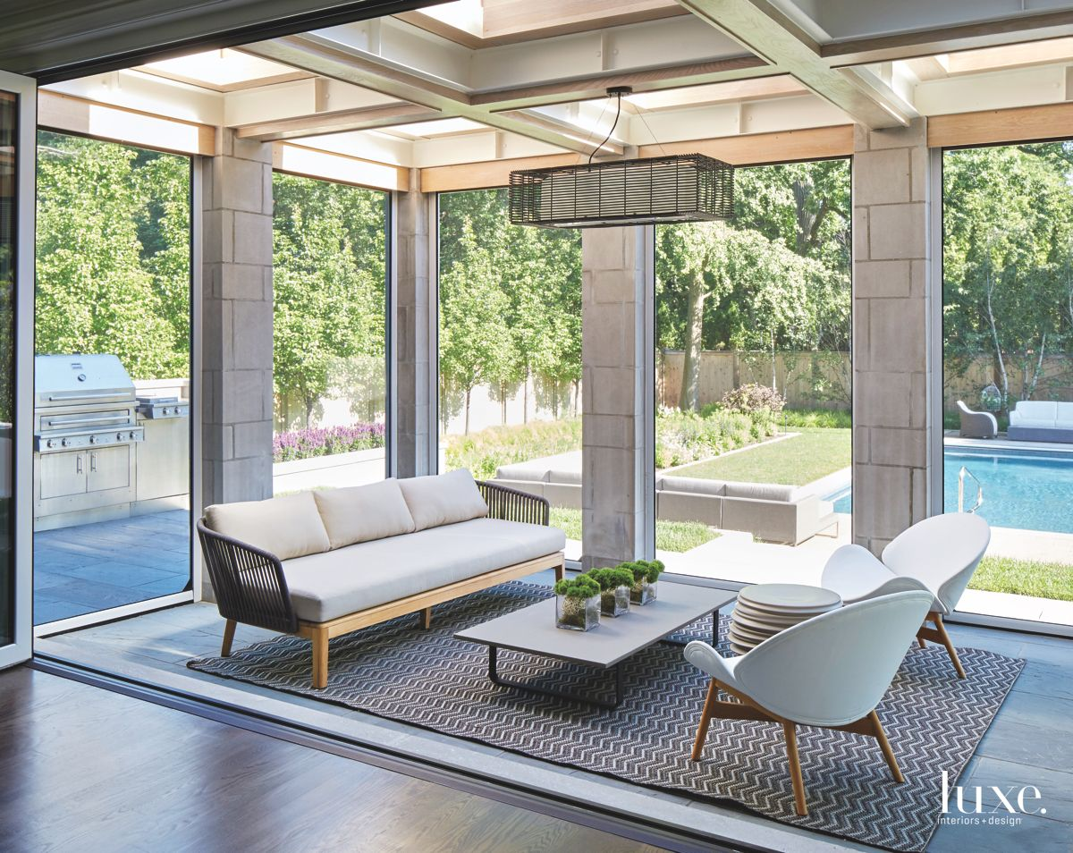 Concrete Sunroom with Floor to Ceiling Windows, Seating, Backyard and Pool VIew