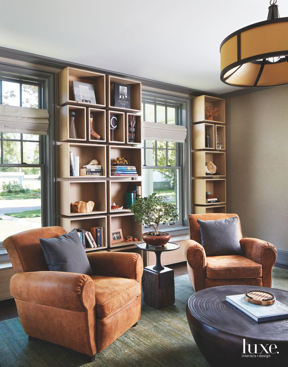 Twin Leather Chair Sitting Area with Library Shelves and Plant