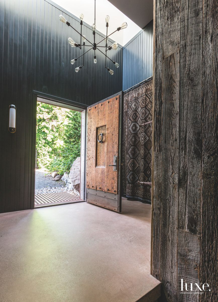 Moody Black Paneling Entrance Foyer with Traditional Door and Contemporary Chandelier