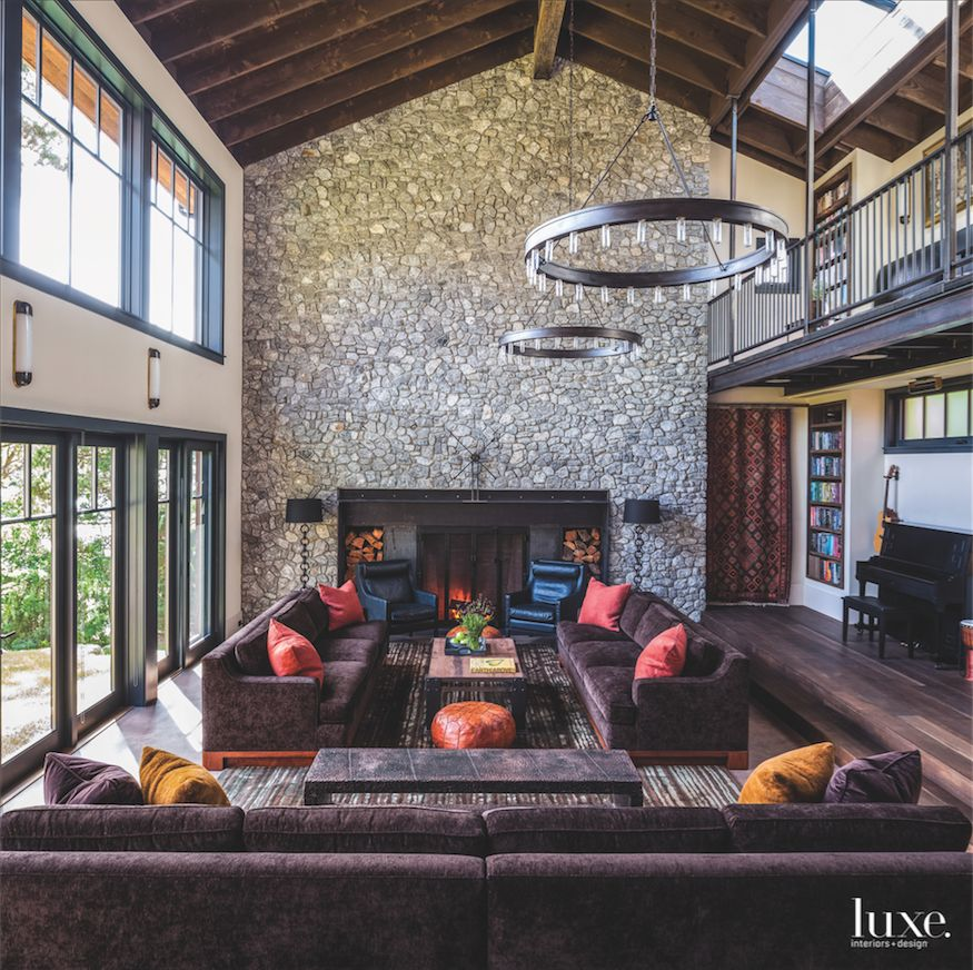 Circular Metal Chandelier Great Room with Stone Wall Fireplace Velvet Couches and Clerestory Windows