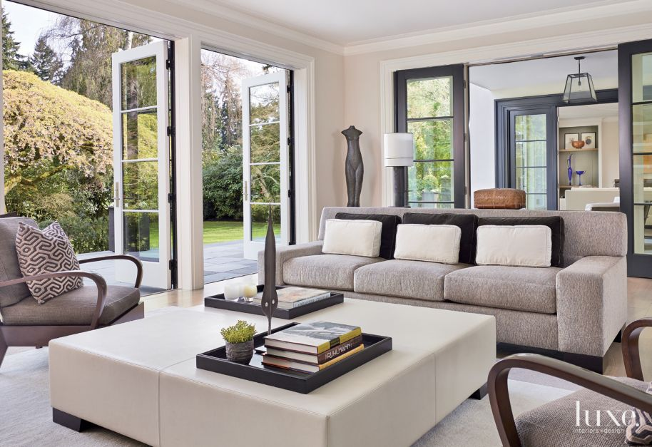 Contemporary white living room with large square ottoman for Magazine living room ideas
