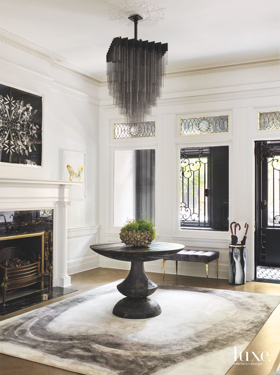 Dramatic Chandelier Entrance Room with Fireplace Artwork and Traditional Mouldings