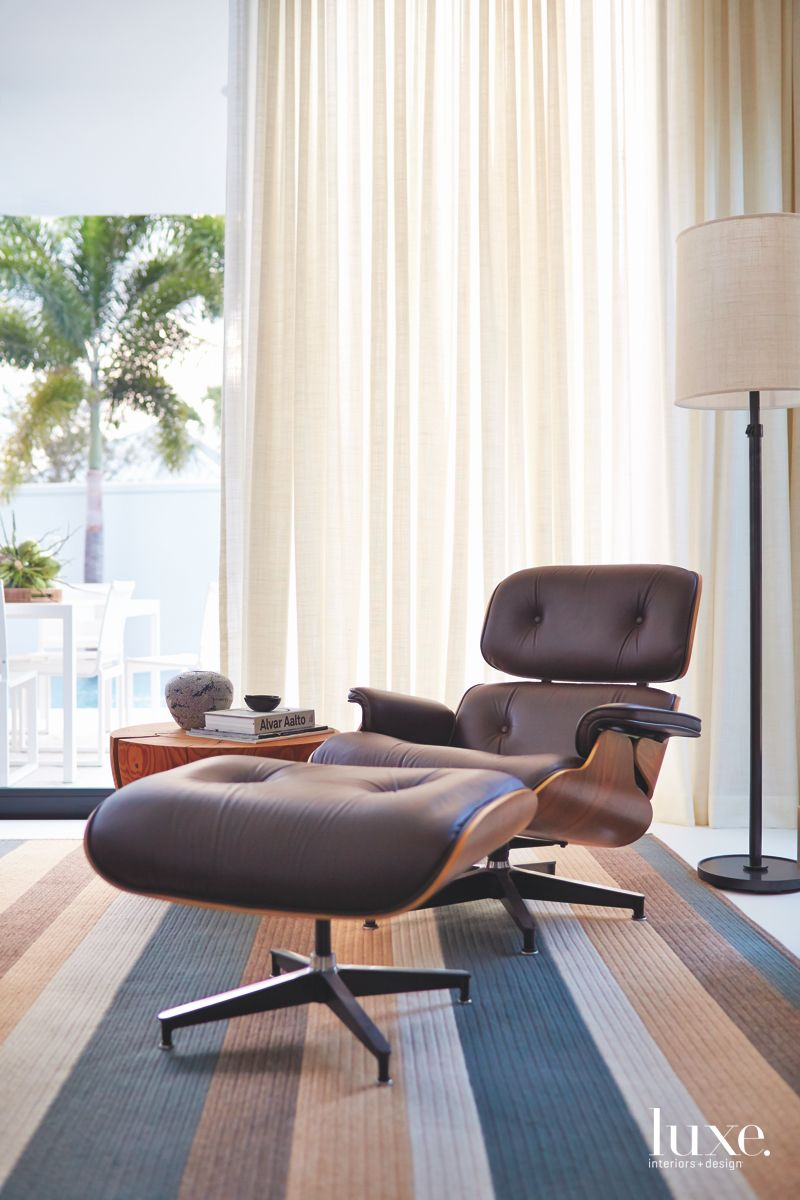 Black Eames Lounge Chair Close Up with Window Backdrop and Palm Trees