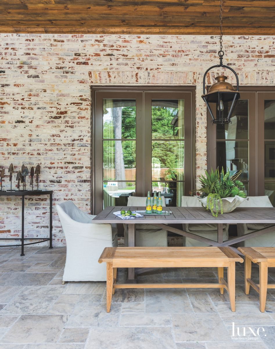 Exposed Brick Outdoor Room with Bench Seating and Lantern Chandelier