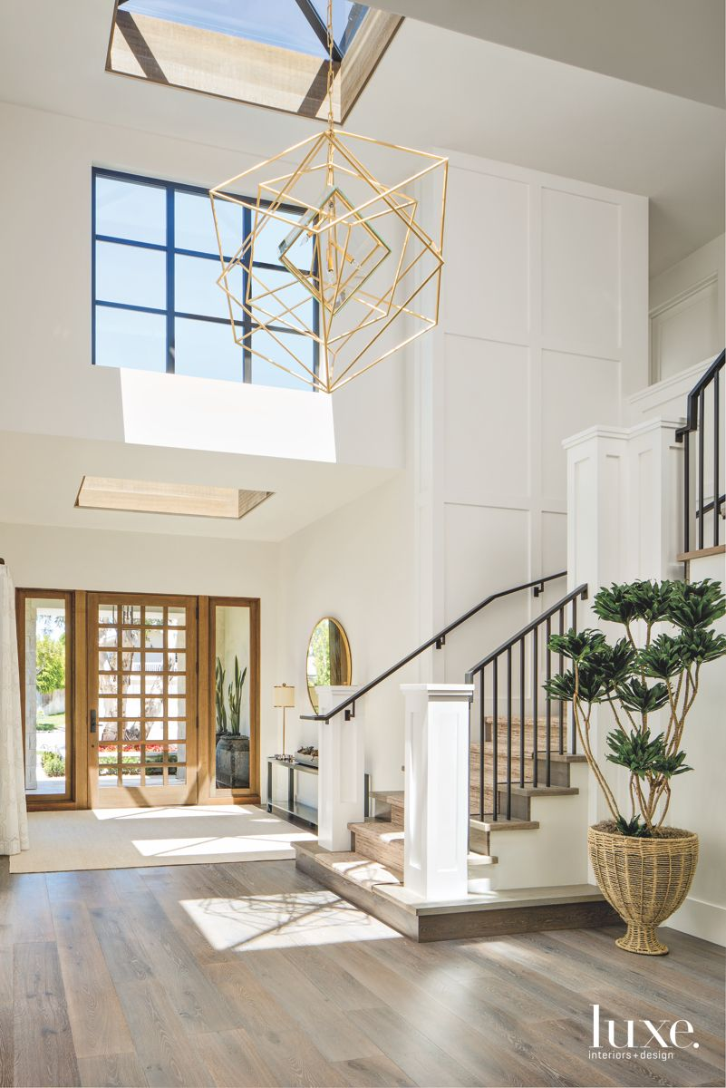 Geometric Light Chandelier Entryway with Staircase and Side Plant
