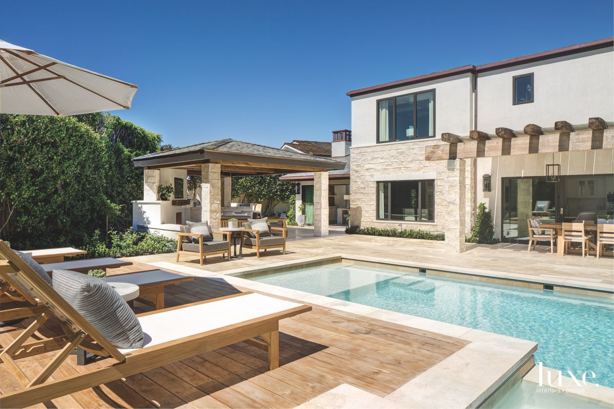 L Shaped Pool Backyard Exterior with Wooden Lounge Chairs Loggia