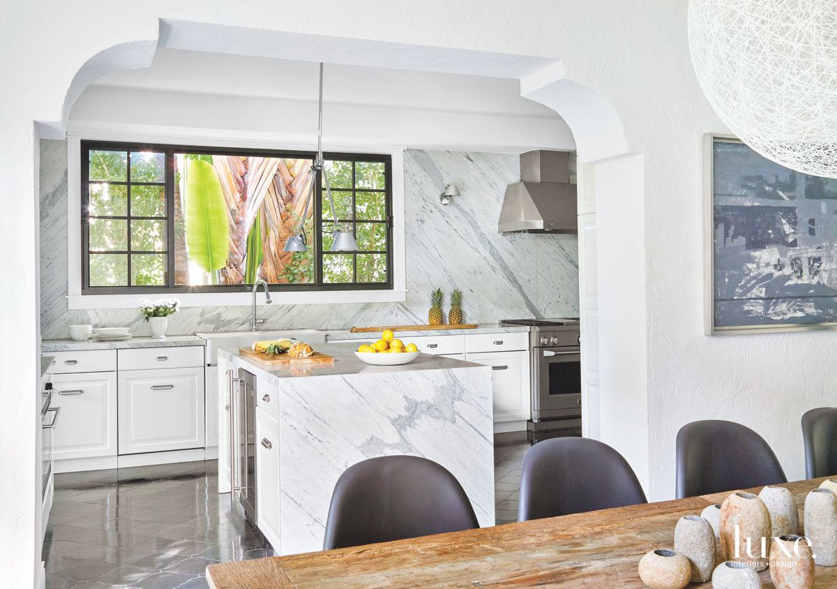 Arched White Kitchen Entrance with Stainless Steel Appliances