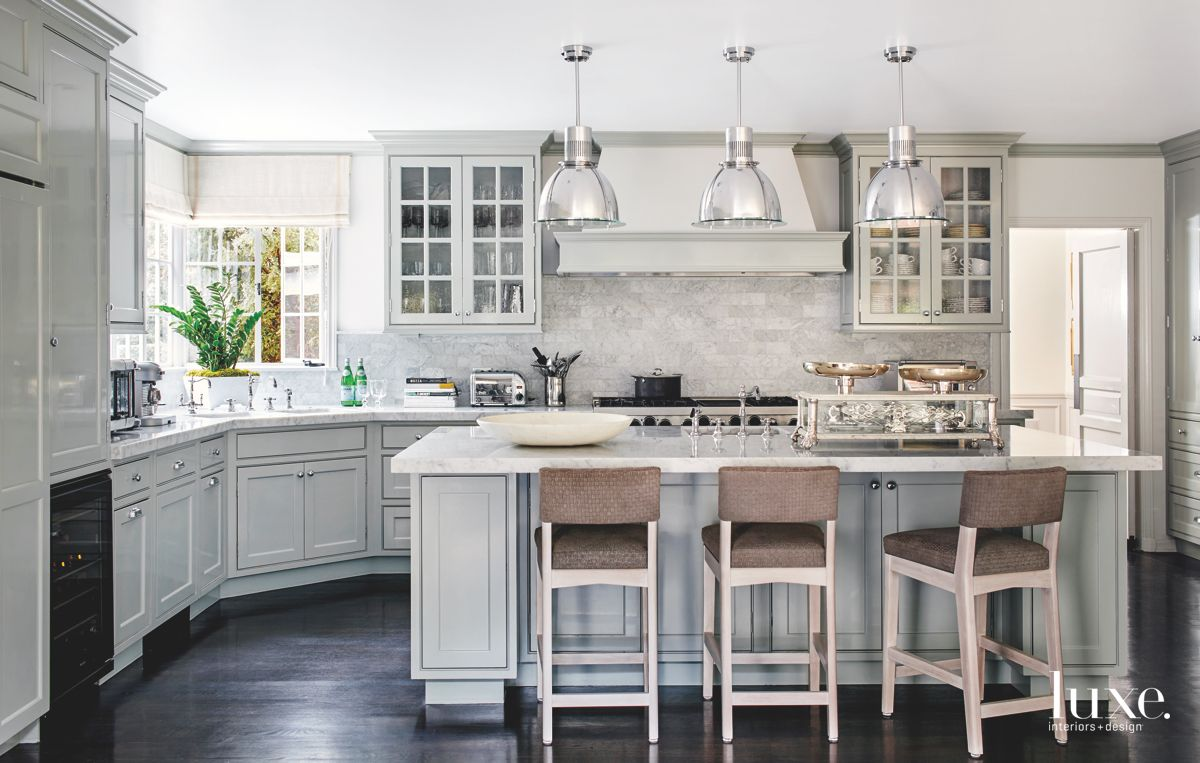 Monochromatic Kitchen with Chrome Light Fixtures and Brown Stools