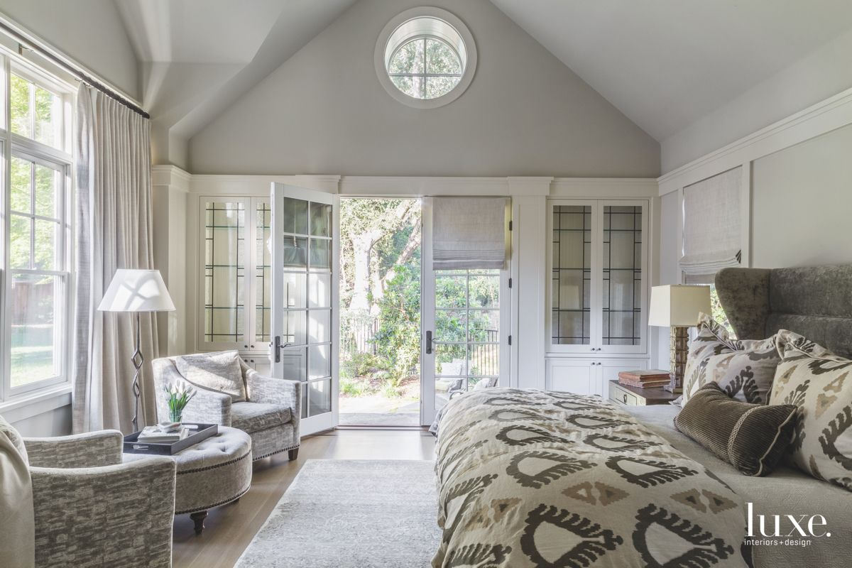 Circular Window Master Bedroom with Open Windows and Doors with Brown Bedding and Seating